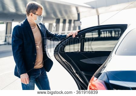 Horizontal Shot Of Man Wears Spectacles And Protective Medical Face Mask, Stands Near Car, Commutes