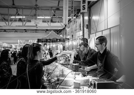 Strasbourg, France - Feb 16, 2020: Side View Of Seller Offering Cheese To Young Girls At French Wine