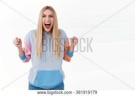 Portrait Of Enthusiastic Attractive Blonde Girl In Hoodie, Chanting, Scream Yes And Smiling, Clench
