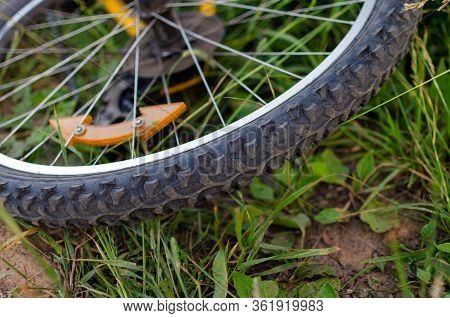 Protectors Of A Yellow Bicycle Wheel Lying On Green Grass. Healthy Lifestyle Concept. Halt Picnic Va