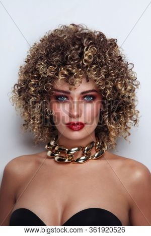 Young beautiful tanned woman with curly afro hair and fancy disco makeup