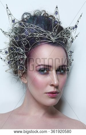 Vintage style portrait of young beautiful woman with fancy makeup and crown on her head