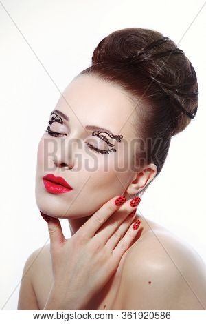 Vintage style portrait of youngbeautiful woman with fancy makeup and hair bun