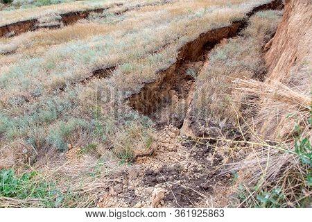 Landslide In An Environmental Meadow Hazardous Crack In Ground Descent Of Large Layers Of Soil Break