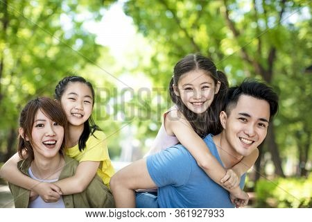 Happy Young Family Having Fun Outdoors Background
