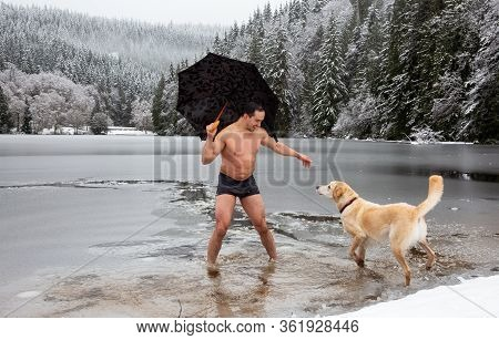 Bizarre Picture Of A Man Holiding An Umbrella And Petting A Dog In A Frozen Lake. Taken In Alice Lak