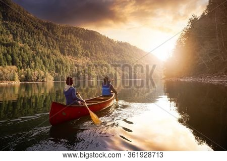 Couple Friends Canoeing On A Wooden Canoe During A Colorful Sunny Sunset. Cloudy Sky Composite. Take