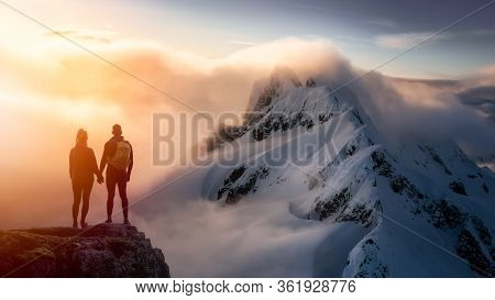 Fantasy Adventure Composite With A Couple Holding Hands On Top Of A Mountain Cliff With Dramatic Lan