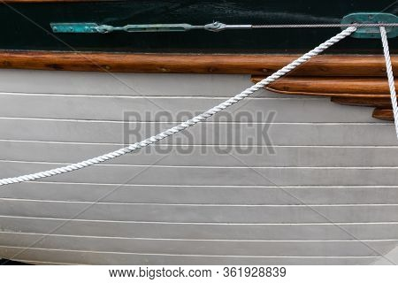 Exterior Hull Of An Old Wooden Boat, Green Patina Hawsehole With Ropes, Creative Copy Space, Horizon