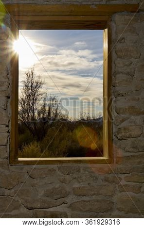 A View Of Desert Plants And A Cloudy Sky Through A Window In A Stone Wall