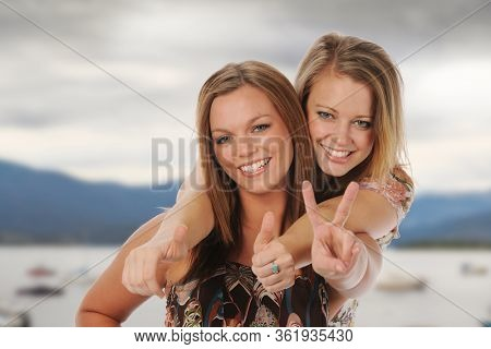 Young women sisters laughing and having fun outdoors