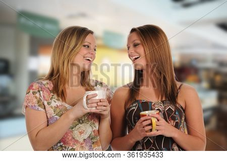 Young women drinking coffee and having fun by a shop indoors