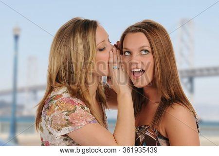 Young beautiful women gossiping outdoors