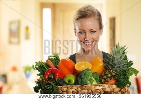 Young Attractive blond woman with fruits and vegetables  inside her home