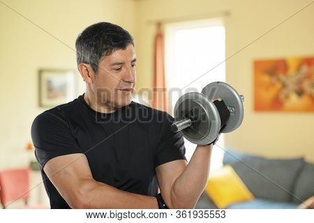 Mature man workingout at home in his livingroom