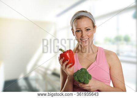 Young beautiful woman holding a brocolli and a pepper inside her house