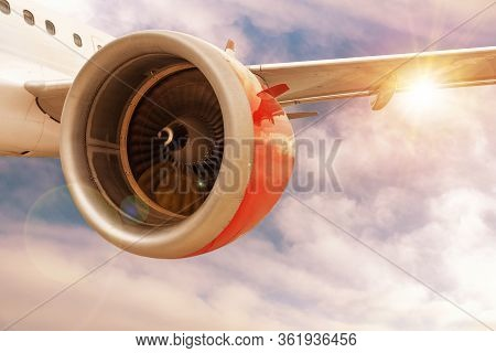 3d Rendering Of Airplane With Red Engine In Flight Through Sunset Or Sunrise Clouds With Lens Flare