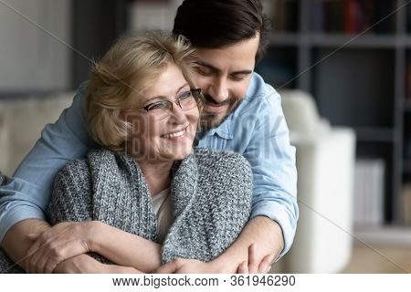 Adult Grown Up Son Hugs From Behind Elderly Mother