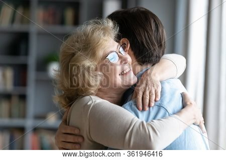 Loving Elderly Mother Cuddles Adult Son Family Enjoy Reunion Indoors