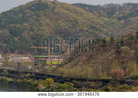 Daejeon, South Korea; April 16, 2020: Landscape Of River Valley With Two Yellow Cranes Over New Buil