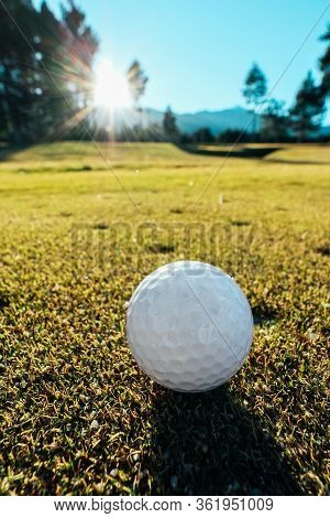 White Golf Ball On A Green Grass Field, Blue Sky, Sunny Morning, Rising Sun, Closeup. Mountains And