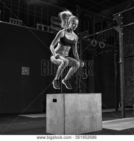 Young Beautiful Girl Jumping On The Box As Part Of Exercise Routine. Fitness Woman Doing Box Jump Wo