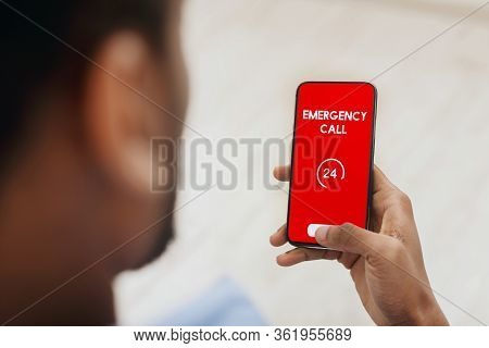 Emergency Call. View Over Shoulder Of Man Holding Phone With 24 Hour Support Line On Red Screen Over