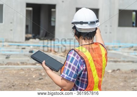 Portrait Of Asian Woman Construction Engineer Worker With Helmet On Head Using Tablet While Standing