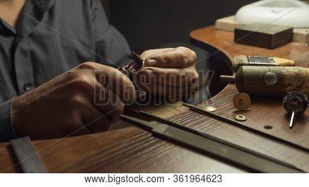 Close-up Of A Hand Of A Goldsmith Polishing A Precious Jewel With Shiny Diamonds. To Make The Jewel