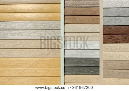 Vinyl Siding With Imitation Wood Texture In Bright Palette Of Colors. Plastic Wall Covering For Exte