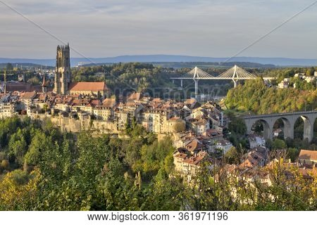 Panoramic View Of Cathedral Of St. Nicholas, New Poya And Old Zaehringen Bridge By Night, Fribourg,