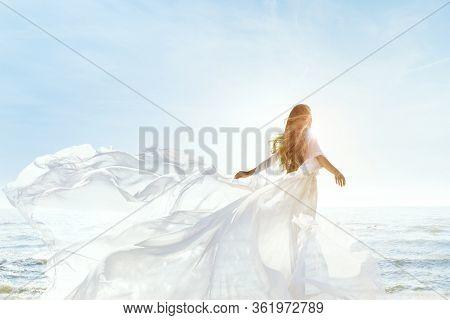 Woman On Sunny Sea Beach In White Fluttering Dress, Fashion Model Back Rear View, Silk Cloth Waving