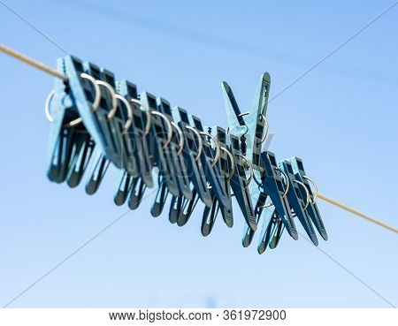 Blue Plastic Clothe Pins On Clothesline Rope