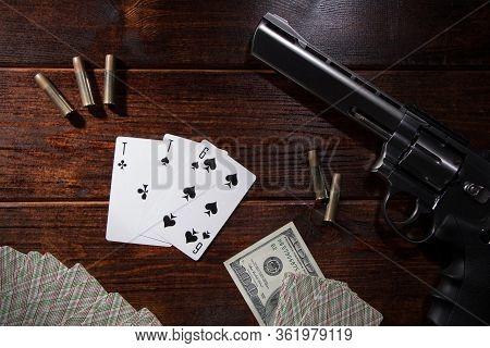 Gambling In Card, Poker Or Blackjack For Money. On A Wooden Table Are A Pistol With Cartridges, Cash