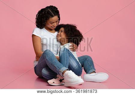 Mothers Warmth. Loving Young Black Mom Tenderly Hugging Her Adorable Little Daughter While Sitting O