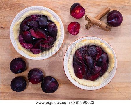 Traditional German Glazed Plum Tart In Miniature Pie Dishes With Cinnamon Sticks