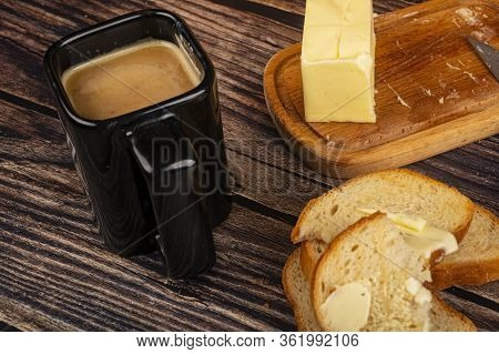 Fresh Wheat Toast With Butter, A Wooden Butter Dish With A Piece Of Butter And A Mug Of Coffee With