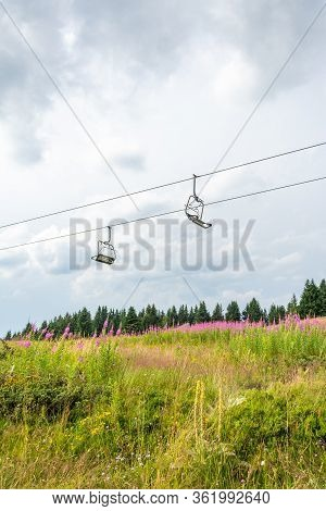 Empty Ski Lift Seats On Cables Above Lush Grassy Summer Mountain Meadow Covered With Flowers And Pin