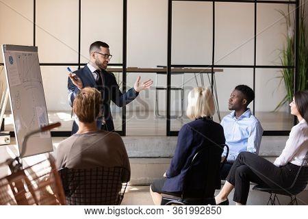 Male Trainer Talk Making Flip Chart Presentation At Briefing