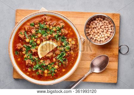 Moroccan Harira Soup In White Plate On Woden Board On Grey Concrete Table Top. Harira Is Moroccan Cu