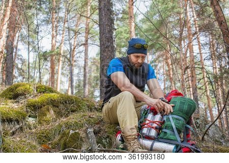 A Man In The Woods Packs His Things In A Backpack. Halt In The Forest. The Concept Of A Healthy Life