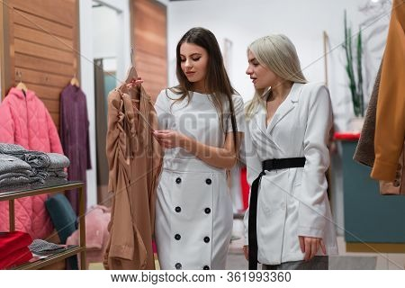 Two Women In Fashion Boutique Choose Dress A Professional Stylist Helps Customers Choose Clothes. Se