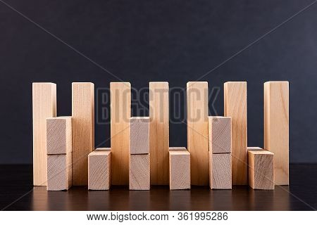 Wooden Tower Of Building Blocks On A Wooden Background, View From The Side. A Concept Of A Game Of S