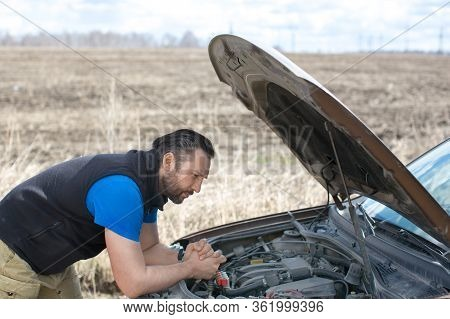 A Man Looks At The Engine Under The Hood During A Breakdown On A Rural Road.