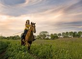 riding teenager and her brown stallion in a field poster