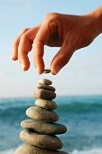 Balanced Stones. Stack of volcanic pebbles on seashore poster