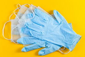Pair Of Latex Medical Gloves And Surgical Ear-loop Mask On Yellow Background. Hygiene Protection Cor