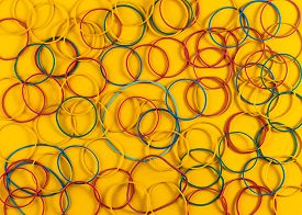 Rubber Bands For Money On A Yellow Background. Colored Rubber Bands For Money On Bright Yellow Paper