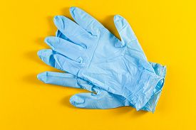 A Pair Of New Blue Latex Protective Gloves Isolated On A Yellow Background. Blue Surgical Gloves. Co