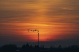 Smoke From A Chimey In A Beautiful Sunset With Industrial Silhouettes